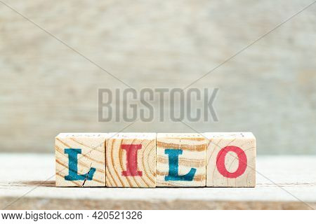 Alphabet Letter Block In Word Lilo (abbreviation Of Last In Last Out) On Wood Background