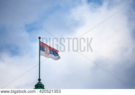 Photo Of The Official Flag Of The Republic Of Serbia, With A Backround Of Blue Sky And Clouds. Serbi