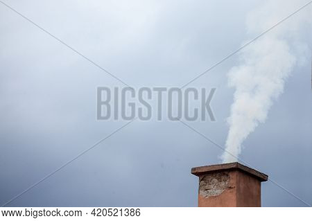 Selective Blur On A Smoking Chimney Rejecting White Fume Brick On The Roof Of An Individual Resident