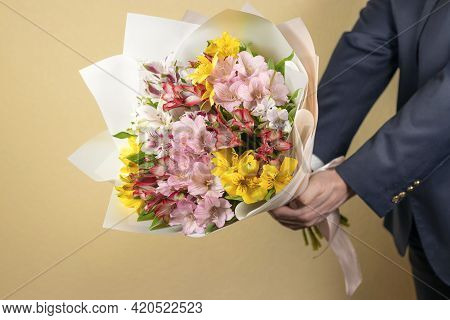 Man In Suit Holds Out A Bouquet Of Multi-colored Flowers. As A Gift Multi-colored Alstroemerias, Pin
