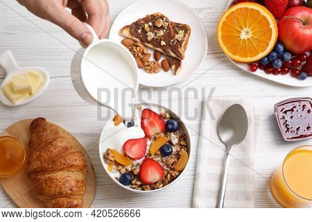 Man Pouring Greek Yoghurt Into Granola At White Wooden Table, Top View