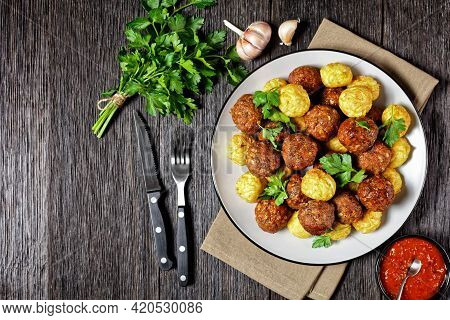 Italian Meatballs Of Ground Beef And Pork With Pasta Balls Served On A Plate With Cutlery On A Dark