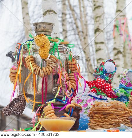 Festively Decorated Table For The Maslenitsa Holiday With A Samovar And Pancakes.