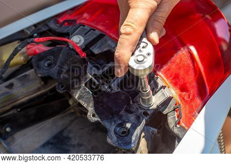 Repair And Dismantling Of A Motorcycle. A Man Unscrews The Trunk Fasteners With A Socket Wrench.