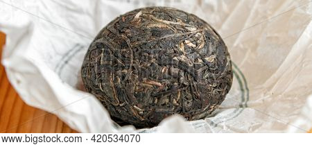 Chinese Raw Pu Er Tea In The Form Of A Nest In A Paper Wrapper