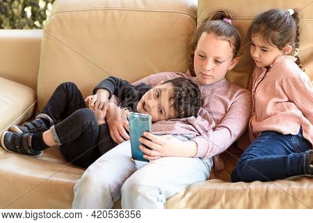 Three Siblings Using A Smart Phone Together.funny Little Girls And Boy Sharing Some Stuff From Smart