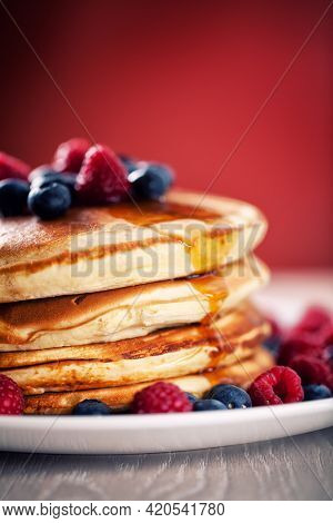 Pancakes With Berries And Maple Syrup On A Plate.