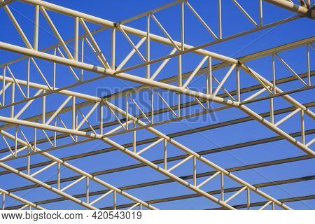 Low Angle View Of Yellow Metal Building Roof Structure In Construction Area Against Blue Sky Backgro