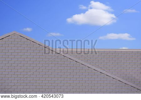 Front View Of Modern Flat Concrete Gray Tile Roof Against White Cloud In Blue Sky Background