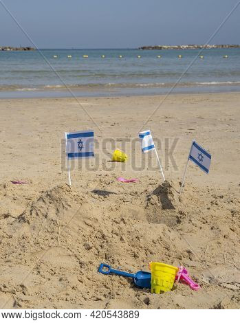 Israeli National Flags On Top Of Sand Piles At The Tel Aviv, Israel, Beach, On A Sunny Day.