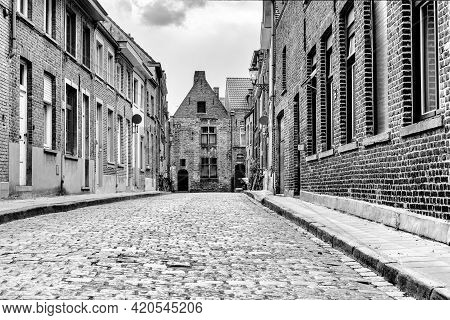 A Black And White Low Angle View Of Typical Brick Buildings In The Historic City Center Of Bruges