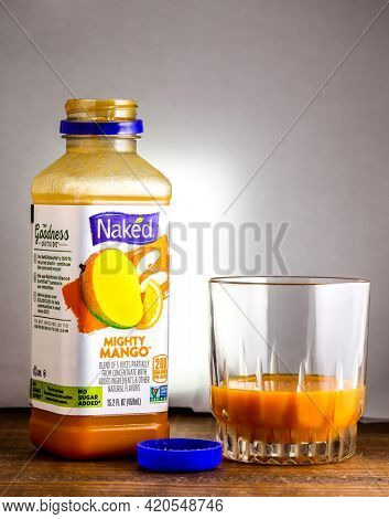 Open bottle with Mighty Mabgo drink from Naked on wooden table