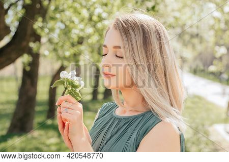 Sunny Sensual Portrait Of A Beautiful Girl Who Sniffs An Apple Tree Flower With Her Eyes Closed