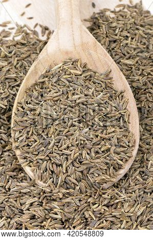 Cumin In A Wooden Spoon Isolated On A Wooden Background. Caraway Seeds. Vertical Orientation.