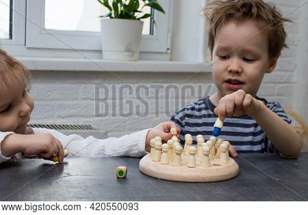 Selective Focus, Face Is Blurred. Wooden Board Game For Children Memory Development. Two Children Pl