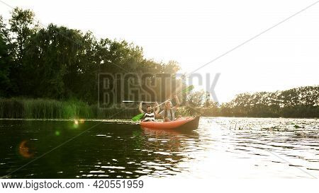 Couple Of Adventurous Friends Kayaking In A River Surrounded By The Beautiful Nature On A Summer Day