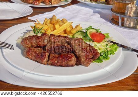 Balkan Cuisine. Cevapi - Grilled Dish Of Minced Meat - With Vegetables