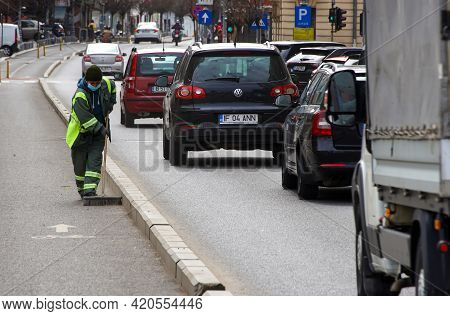 Bucharest, Romania - April 15, 2021: An Woman Janitor Worker Sweeps The Garbage From A Bicycle Track
