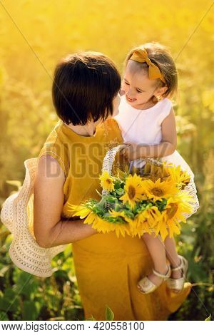 Grandmother And Granddaughter In A Field Of Sunflowers Hold A Basket Of Flowers And Cute Emotional C