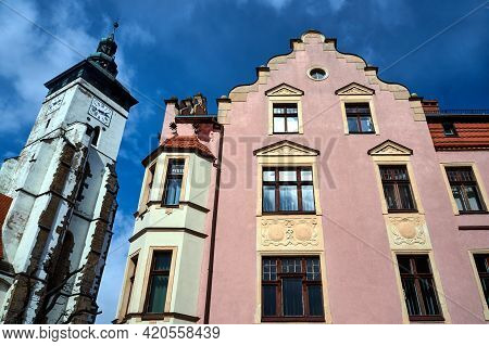 The Facade Of A Historic Tenement House And The Belfry Of A Medieval Church In The Town Of Zlotoryja
