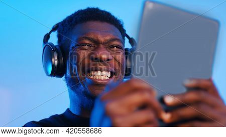 African American Black Man With Headphones Making Intense Face Expressions While Using Tablet. High