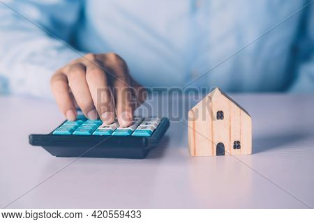 Hand Of Businessman Planning And Calculate Expense And Mortgage With Calculator And Home On Desk, In