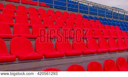 Bleachers In A Sports Stadium. Red And Blue Seats In A Large Street Stadium