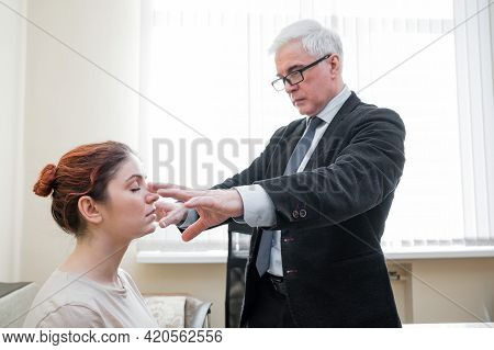 Mature Gray-haired Man Hypnotizes Caucasian Woman During Hypnotherapy Session. The Psychologist Uses