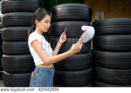 Young Asian Owner Of The Auto Parts Store Check The Number Of Tires And The Incoming Orders Before S