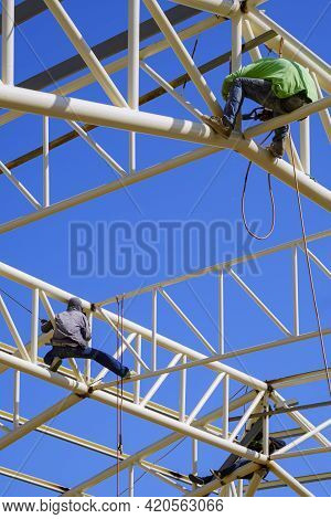 Low Angle View Of Asian Construction Workers Group Welding Metal On Roof Building Structure Against