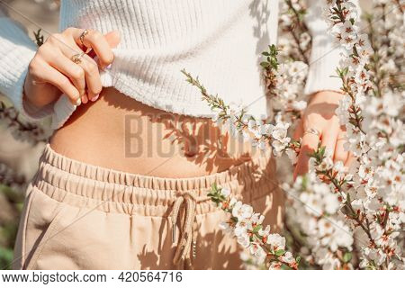 Partial View Of Beautiful Slender Woman In Delicate Clothes Posing With Hands Near Her Belly And Wit