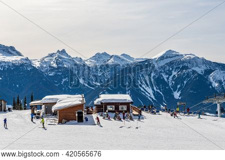 Revelstoke, Canada - March 17, 2021: People On Downhill Ski Trail Cable Lift Station.
