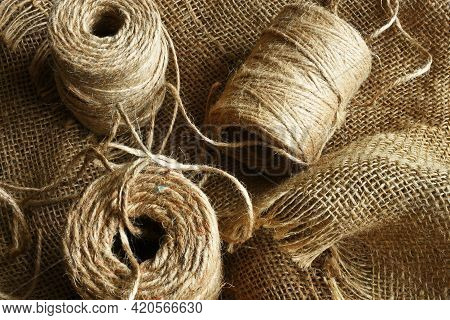 A Close Up Image Of Coils Of Beige Burlap String On Burlap Fabric.