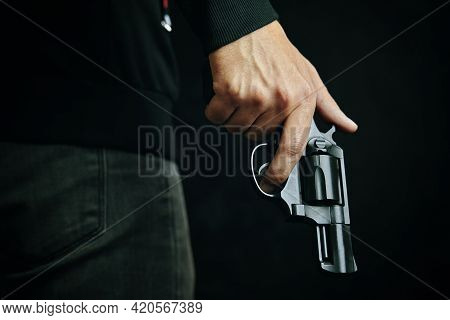 Guy With Gun Down. Black Revolver With Drum In Mans Hand. Armed Person On Dark Background. Firearms