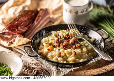 Slovak National Dish Bryndzove Halushky Served Next To Bacon And A Gcup Of Milk.