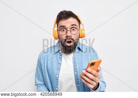 Amazed Bearded Adult Man Stares Bugged Eyes Cannot Believe Something Holds Mobile Phone Listens Musi
