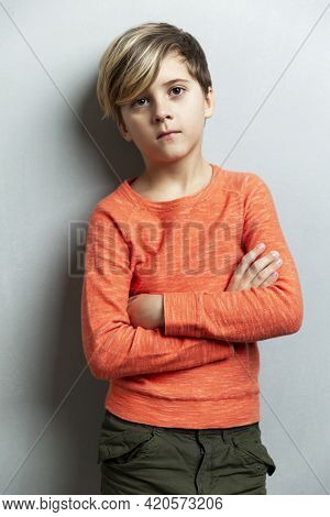 A Serious Boy Of 9 Years Old In An Orange Jacket Stands Against The Wall. The Arms Are Crossed Over