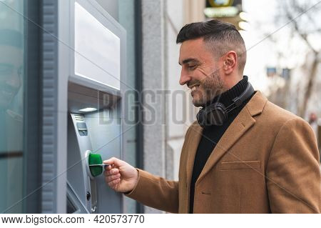 Spanish Man Getting Cash From Atm. Latino Man Using Credit Card At Atm. Lifestyle Concept.