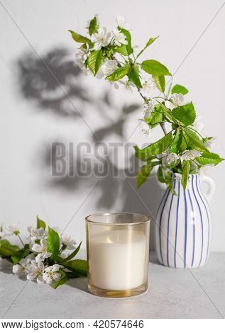 Scented Candle And Cherry Tree Blossoms In Vase On Table. Gray Background With Long Shadows. Cozy Sp