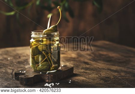 Capers. Marinated Or Pickled Canned Capers Fruit In Glass Jar On Wooden Table, Eco Style Still Life