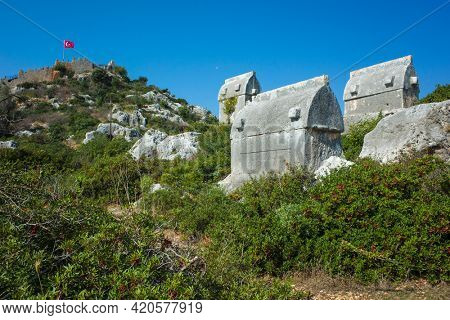 Lycian rock tombs, Rock sarcophagus at ancient Lycian necropolis on hill and fortress Simena with Turkish flag in Simena (Kalekoy), Turkey