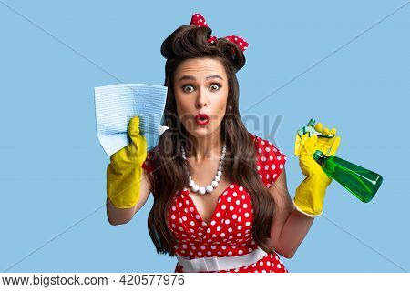 Surprised Pinup Lady In Retro Clothes Cleaning Screen With Rag, Using Spray Detergent On Blue Studio