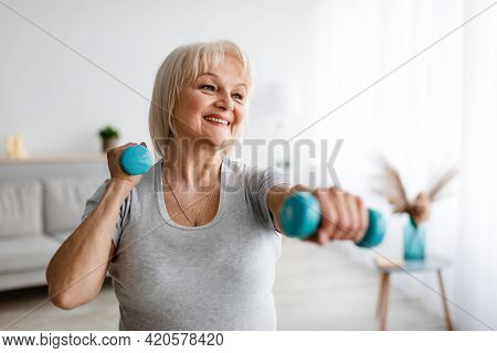 Mature Woman Exercising At Home With Two Dumbbells