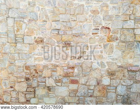 Masonry concept. Old weathered exterior rough strong stonewall background texture. Cobblestone, floor beige brown grey empty for backdrop. Rocks connected with cement solid construction. Border fence.