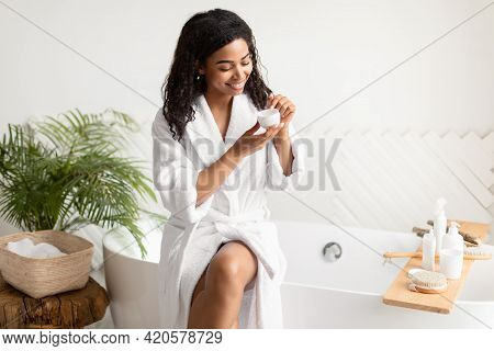 Black Lady Holding Moisturizer Cream Sitting On Bathtub In Bathroom