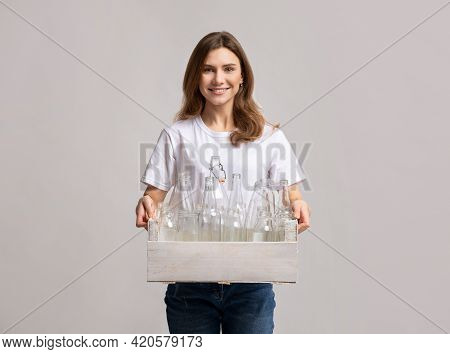 Domestic Waste Reuse. Smiling Lady Carrying Wooden Box With Empty Glass Bottles
