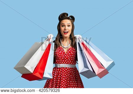 Excited Young Pinup Woman In Red Polka Dot Dress Holding Lots Of Shopping Bags On Blue Studio Backgr