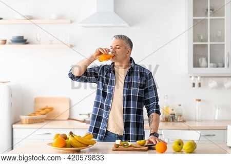 Healthy Eating. Mature Man Drinking Fresh Juice, Standing Near Table Full Of Various Fruits In Kitch