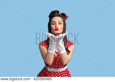 Lovely Young Pinup Lady In Stylish Retro Dress And Bright Makeup Blowing Air Kiss At Camera Over Blu