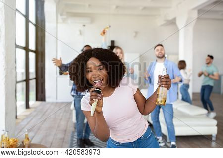 Young Black Woman With Beer Bottle And Microphone Singing Karaoke With Fellow Students At Home